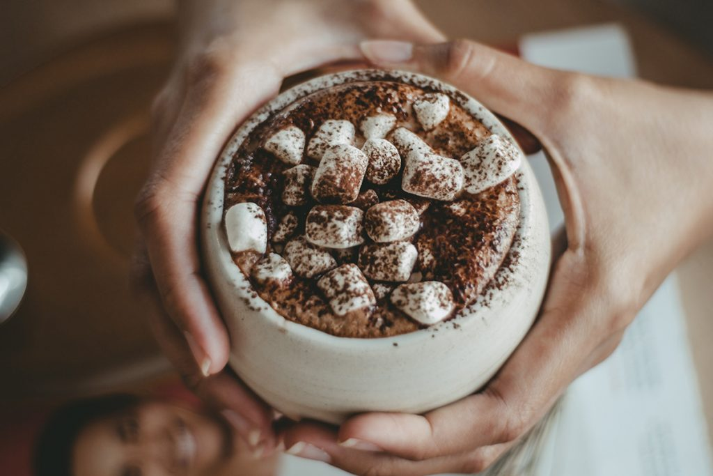 person holding white cup with marshmellows