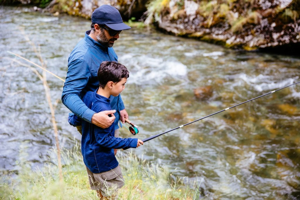man in KÜHL shirt and KÜHL hat fishing with his son next to river
