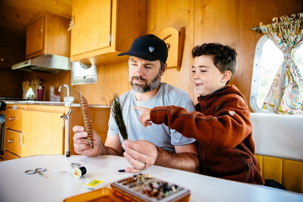 man in KÜHL shirt showing feathers to his son in camper