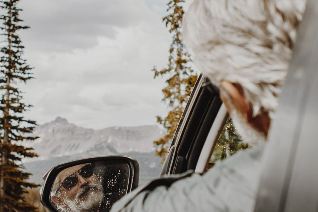 man with gray hair and beard reflecting in car mirror