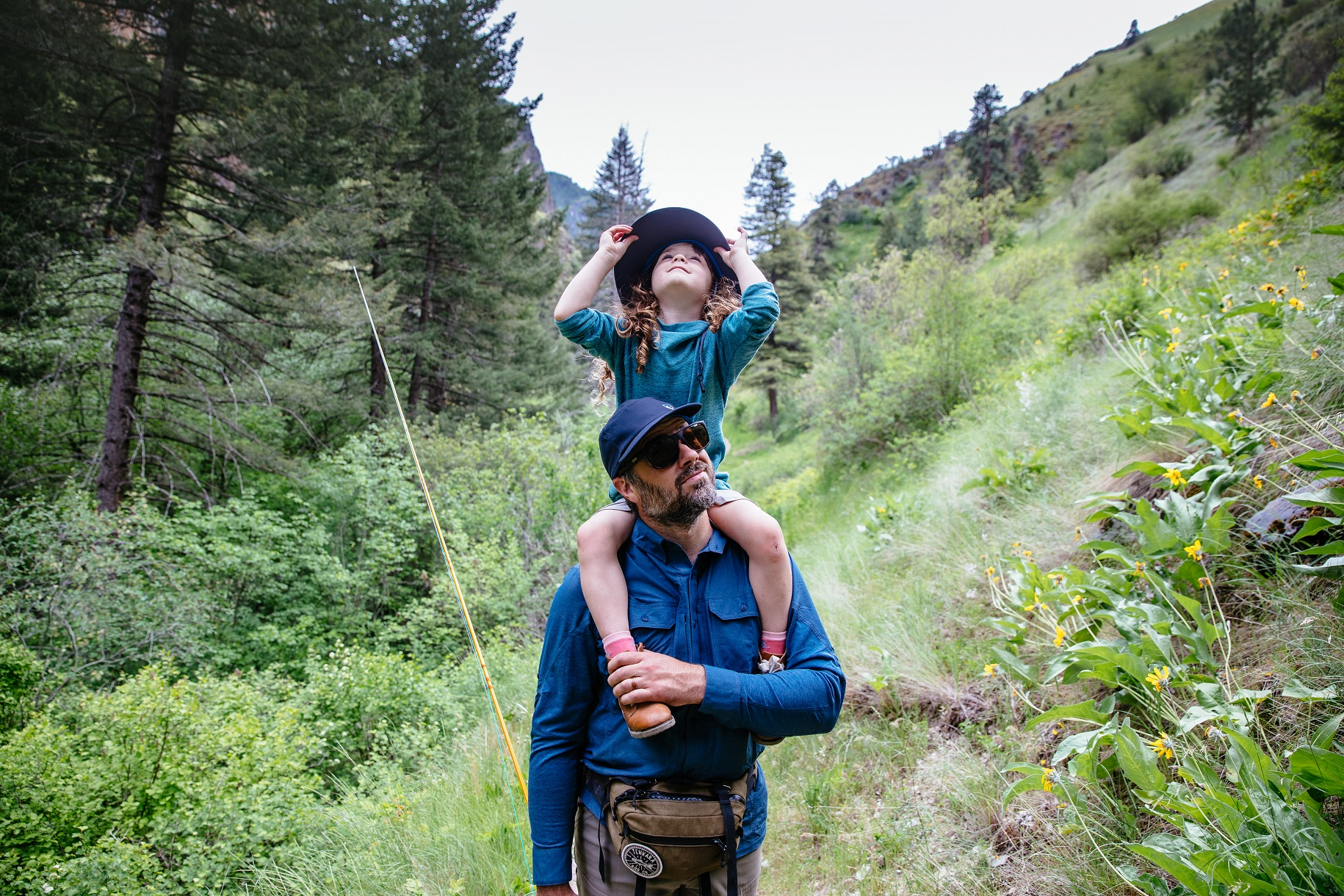 man in KÜHL shirt and KÜHL hat carrying daughter on his shoulders