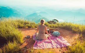 woman sitting on red picnic blanket on mountain top