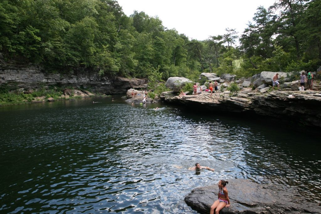 people bathing in the body of water surrounded by rocks