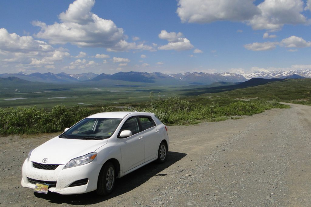 white car at the road near mountains
