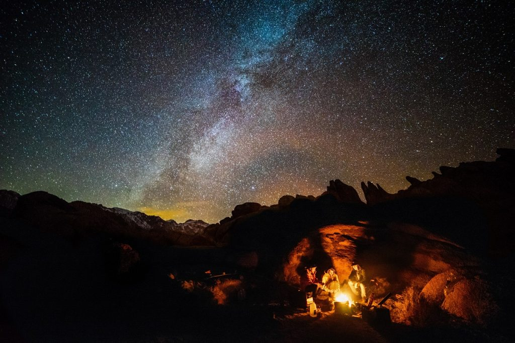 people camping next to fire under starry sky