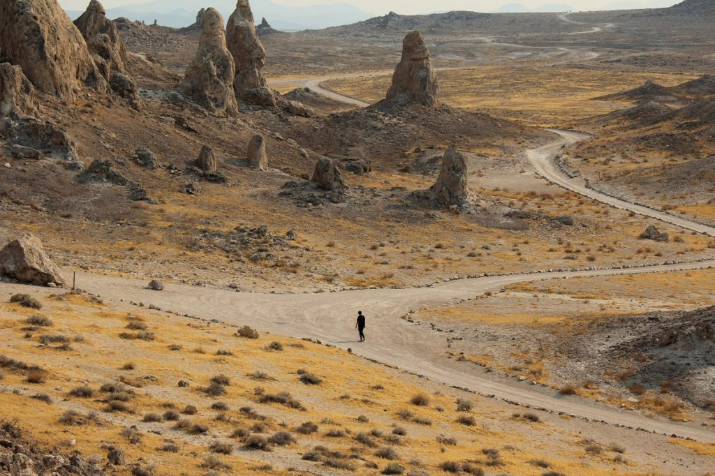 dirt roads next to brown rock formations