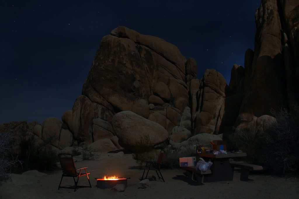 camp site under brown rock formation during night