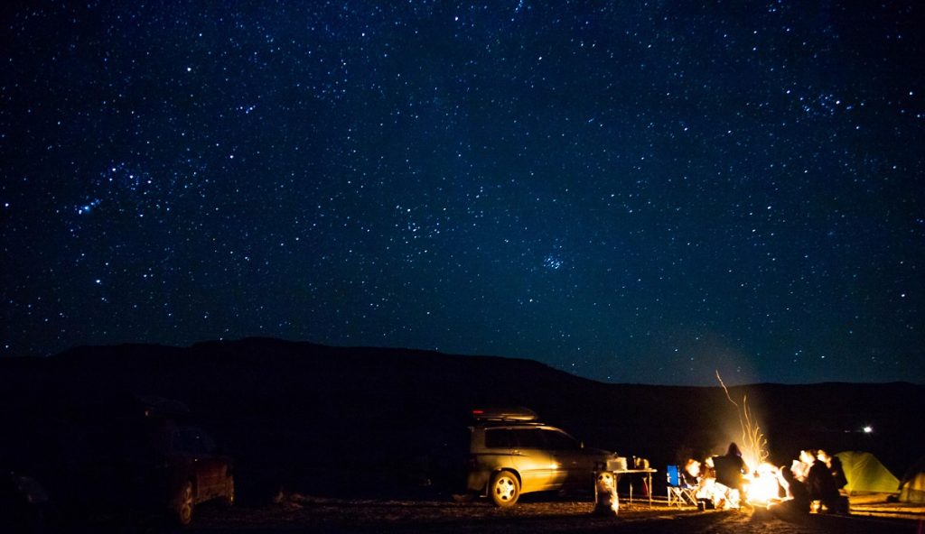 people sitting around the camp fire under night sky