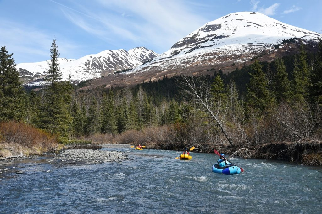 people packrafting on the river with snowy mountain peak in the back