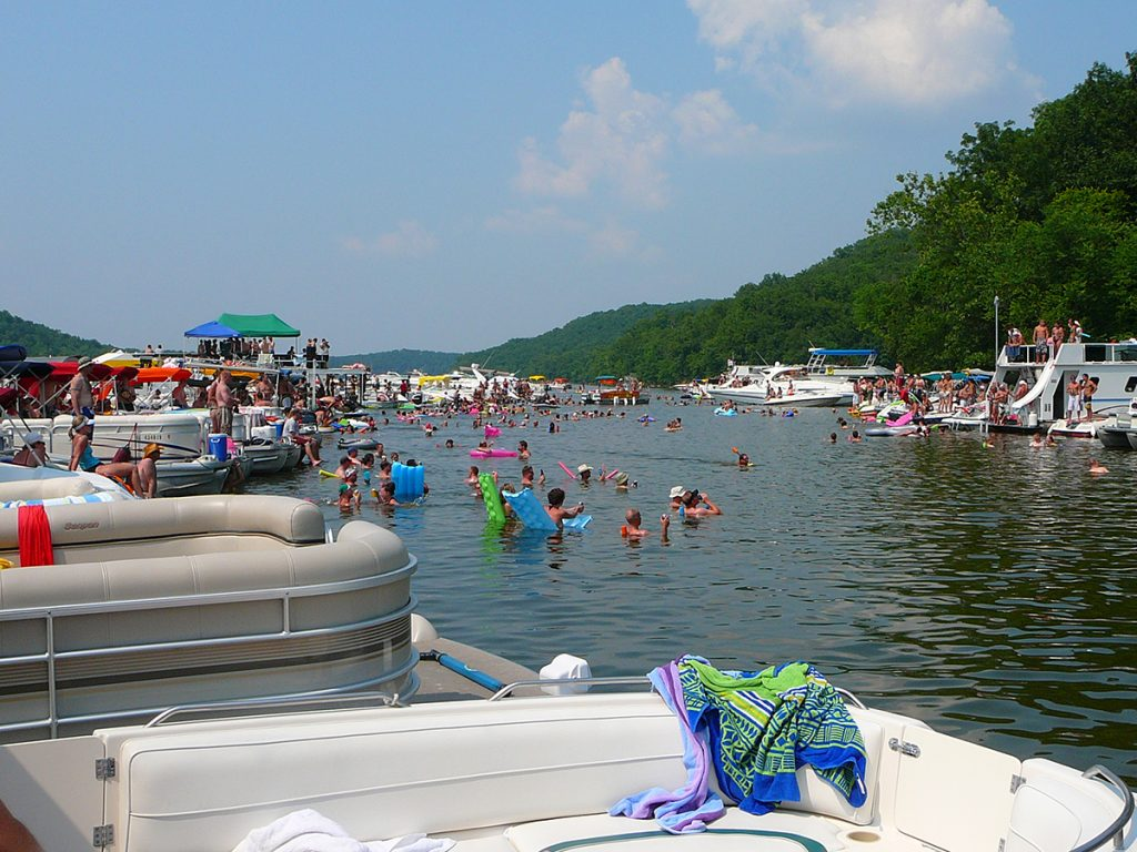 pontoon boats and people in body of water