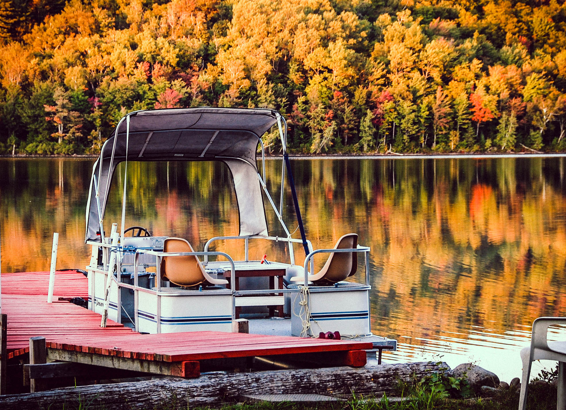 white pontoon boat on body of water with yellow trees in background