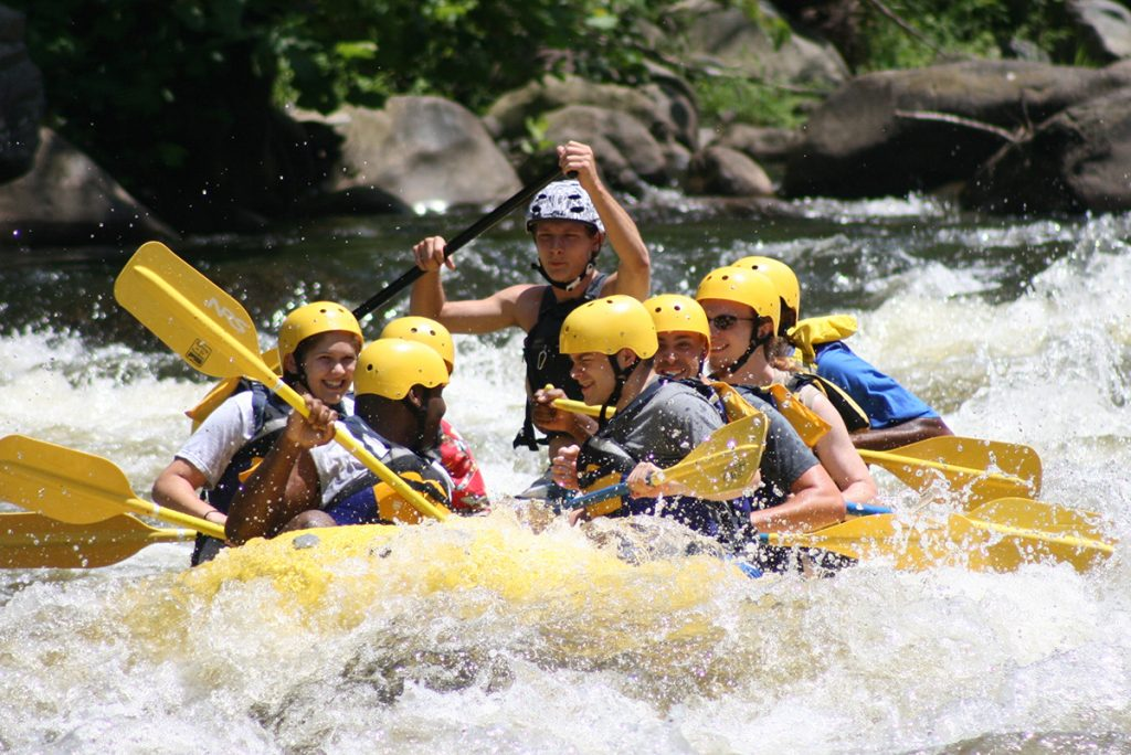 people whitewater rafting in yellow boat