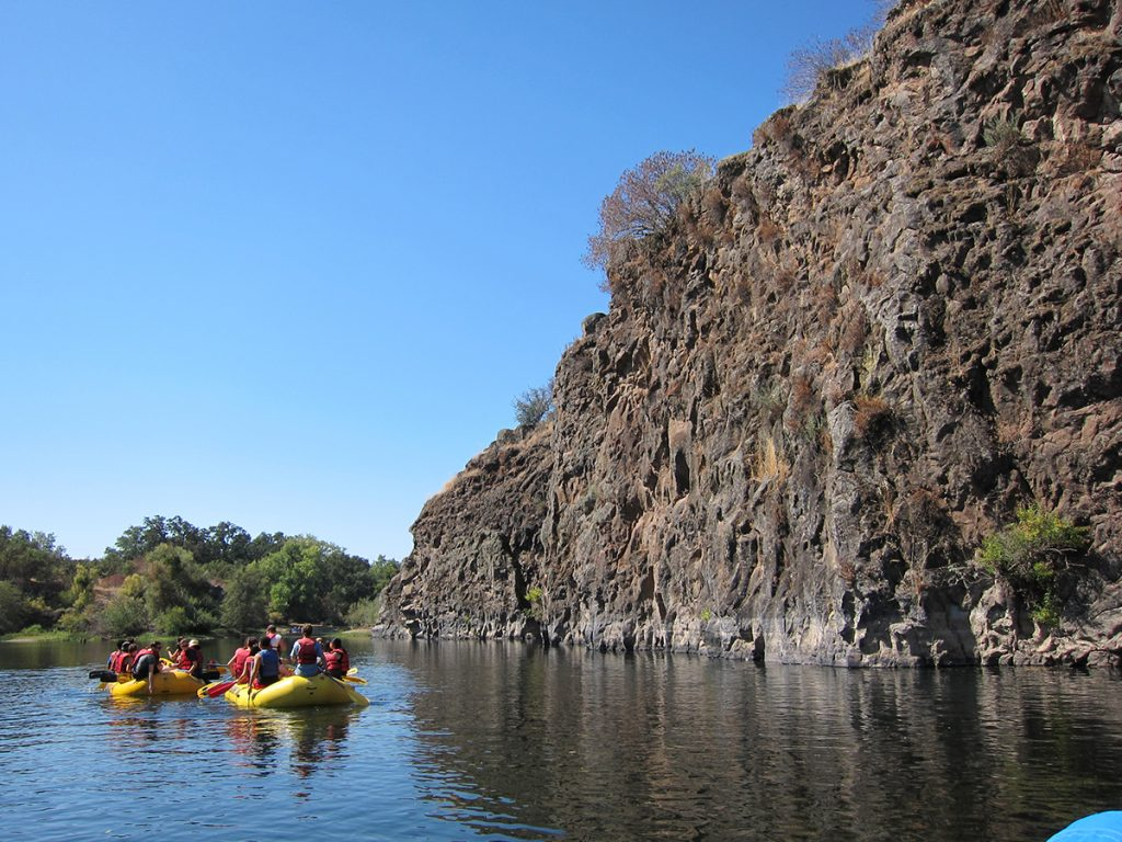 yellow boat rafting next to rocky cliff
