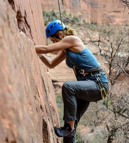A woman in KUHL hiking pants climbing a cliff