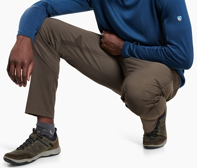 A man in KUHL hiking pants showing gusseted crotch feature