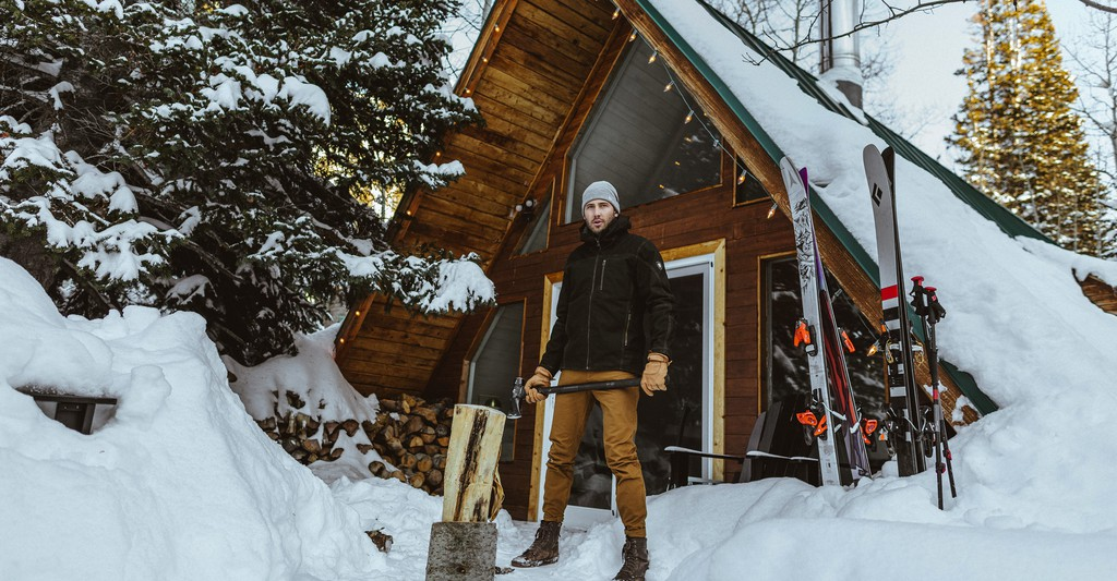 A man standing in snow in front of a cabin wearing KUHL clothing from gifts for him
