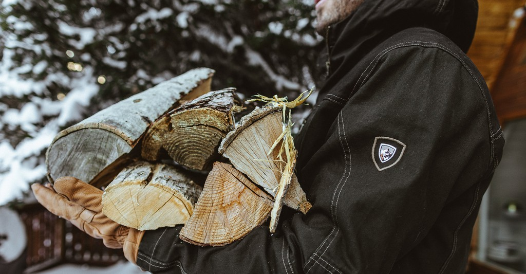 A man carrying firewood in KUHL clothing you can purchase for his craft