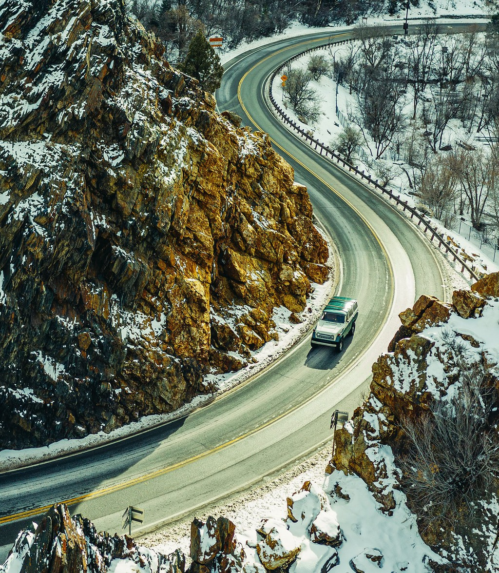 A car goes down a snowy road that meanders on a mountain