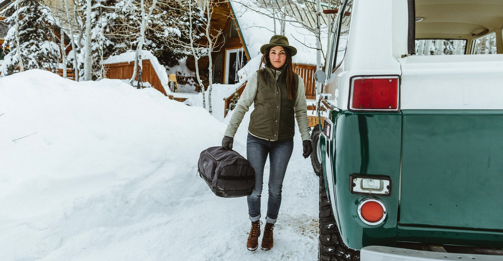 A woman carrying KUHL travel bag gets ready to get on the bus in KUHL clothing gifts for female travelers