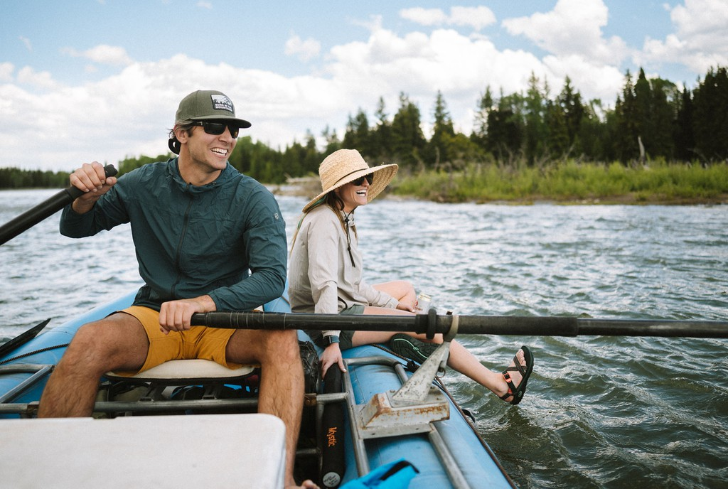 Man and woman enjoying a boat ride in outdoor clothing - Taken from KUHL Clothing Home Page