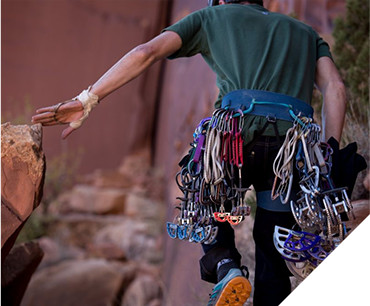 A man carrying climbing gear at Zion National Park, dressed in KUHL men's climbing clothing