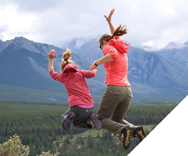 KUHL Ambassador Nicole and a girl jumping in the great outdoors, dressed in KUHL hiking clothing