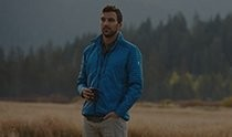 Man in a field with a forest in the background, wearing KÜHL outdoor clothing - men's hiking pants and men's outerwear.