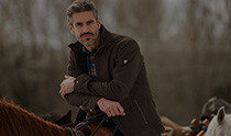 Man riding a horse, dressed in KÜHL men's outerwear.