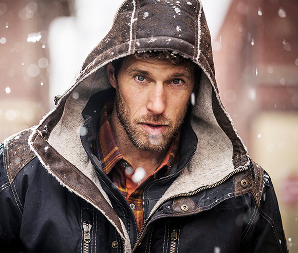A man looking at the camera, wearing KUHL men's Arktik Down Jacket with the hood up