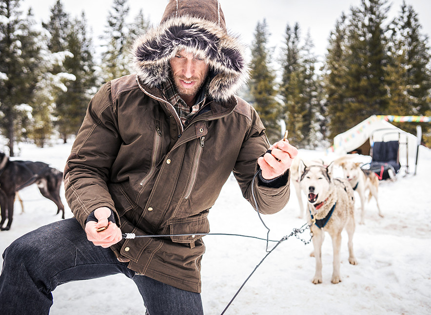 A man dressed in KUHL Arktik Jacket, with sled dogs ready behind him