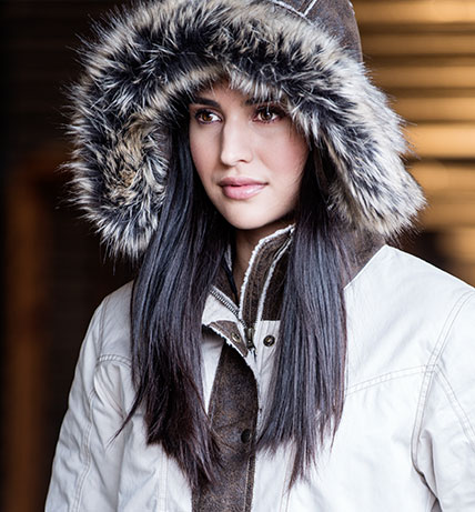 An interior image of a black haired woman wearing KUHL women's Arktik Down Jacket with the hood up