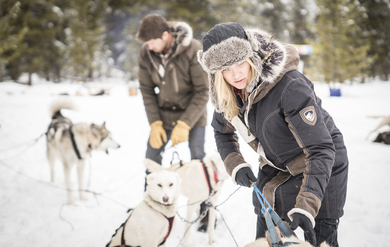 A woman checking the dogs and sleads, dressed in KUHL women's Arktik Down Parka.